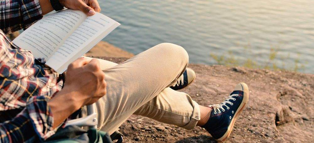 homme avec un livre devant une falaise